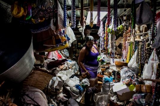 Un magazzino al centro dell'Havana dove una donna sistema amuleti, collane, suppellettili legati al culto degli orisha